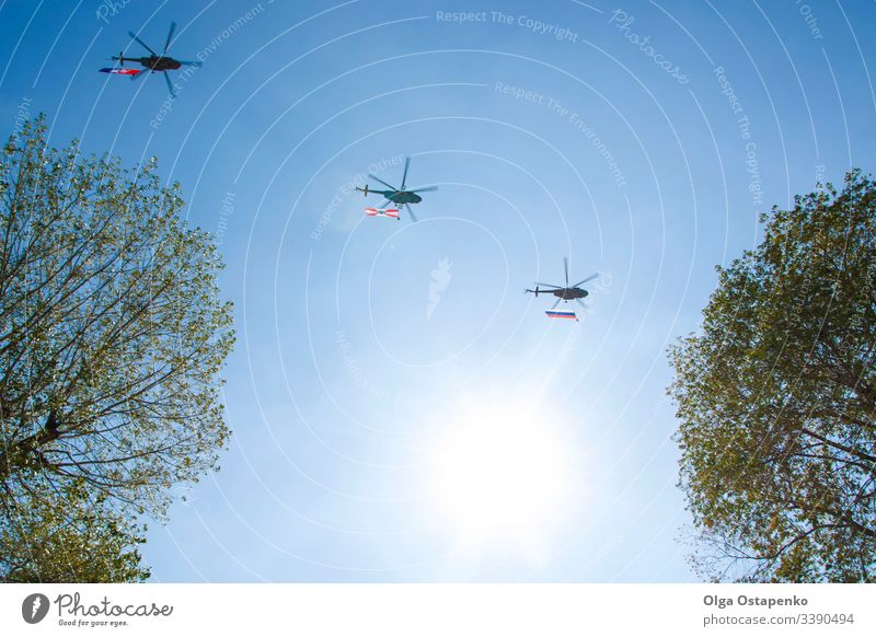 Drei graue Militärhubschrauber fliegen am blauen Himmel. Sie tragen Flaggen mit sich. Demonstration eines friedlichen Fluges. Tag der Stadt. Erinnerung. Hintergrund mit Kopierraum für Text. Flugschau