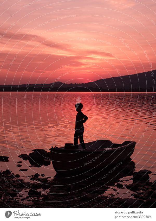 Sonnenuntergang auf einem See mit einem Kind in einem Boot Sonnenuntergangssee Silhouette eines Kindes rot purpur Mensch Junge Abend blau Himmel Steine Wolken