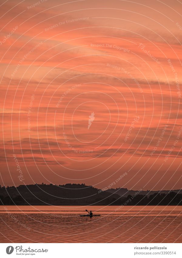 Kanu bei Sonnenuntergang Sonnenuntergangssee Boot Silhouette rot purpur Mensch Abend blau Himmel Steine Wolken Schatten Wasser Berge Berge u. Gebirge Stimmung