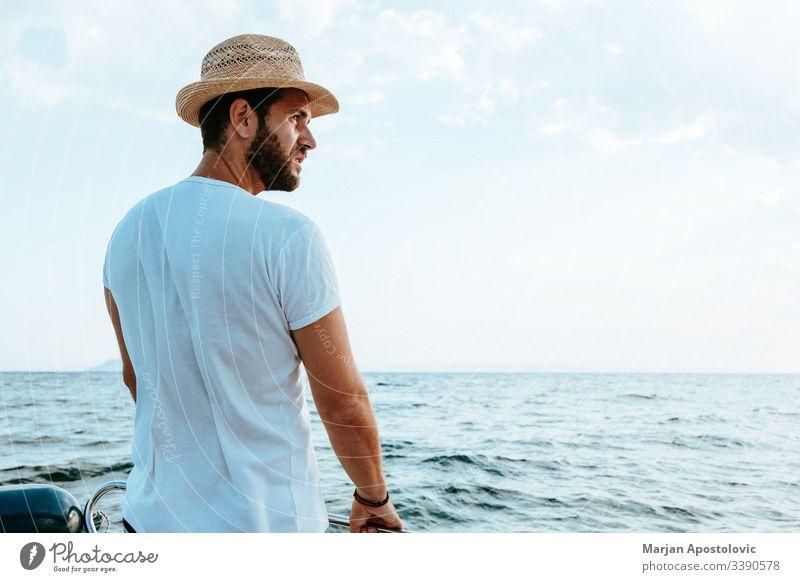 Junger Mann genießt eine Fahrt auf einem Boot auf dem Meer jung gutaussehend bärtig lässig Abenteuer MEER Wasser Wellen Kreuzfahrt speedbo nautisch männlich