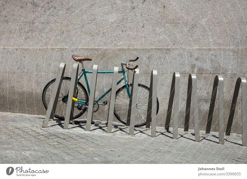 Rennrad an Fahrradständer vor grauer Wand Türkis blau grün Rad fahrrad Fixie rennrad citybike bicycle Reifen rahmen lenker mantel ventil klingel Ständer
