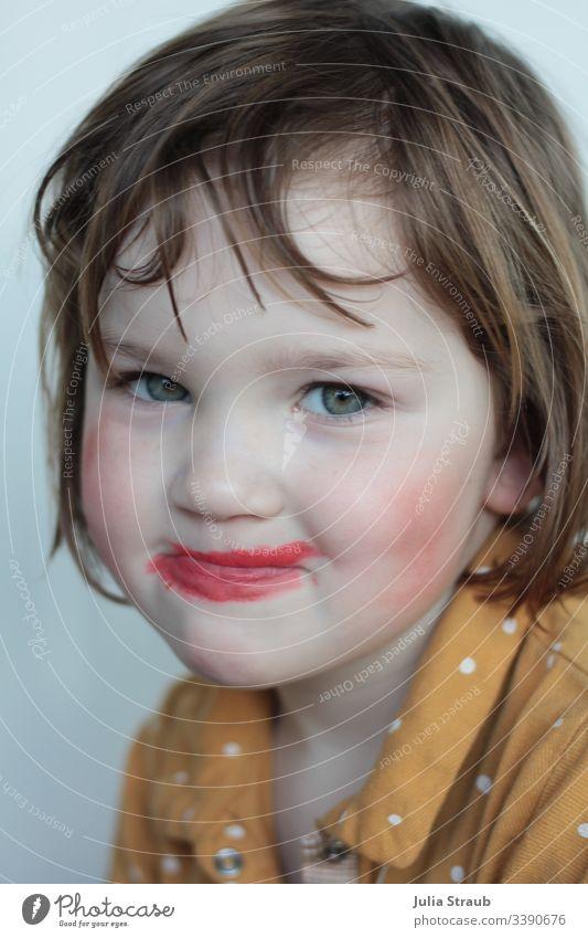 Kind hat sich selbst geschminkt Kindheit Spaßvogel Kreativität grüne augen klare Linien roter lippenstift Lippenstift schick Schickimicki schnute ziehen schief