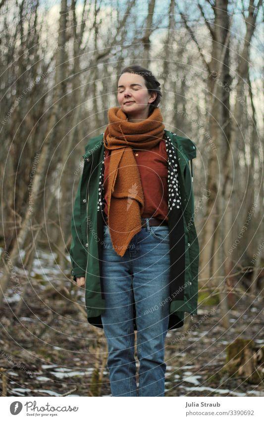 Frau steht im Wald mit geschlossenen Augen Bäume Wolken Mantel Schal hemdbluse Jeanshose gepunktet atmen geschlossene Augen Gürtel ockerfarben Grün