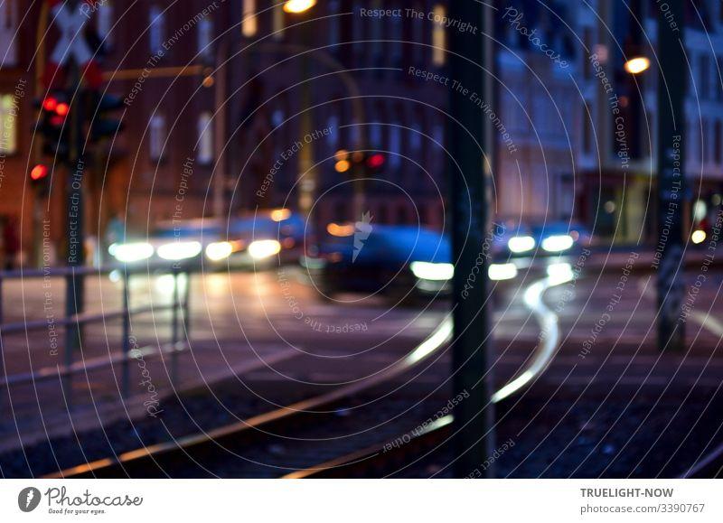 Straßenkreuzung am Abend mit Ampeln, Autos, die mit Licht fahren und elegant gebogene Tram-Schienen, die das Scheinwerferlicht reflektieren. Im Hintergrund ein großes Eckhaus aus dunkelroten Backsteinen.