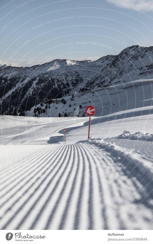 Pistenmarkierung im Neuschnee an frisch präparierter Piste Panorama Berge Schnee Tellerlift Skifahren Tal Powder Anfänger kalt Sonnenaufgang Spuren Gebirge