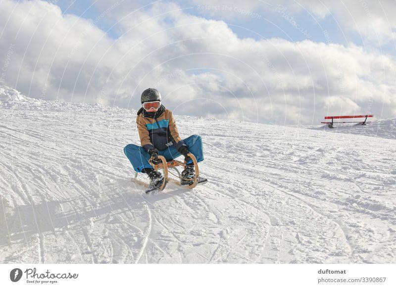 Junge auf Schlitten in Schneelandschaft Rodel rodeln schlittenfahren lustig schnell Winter Abfahrt Spaß kalt aussen draußen Vergnügen Piste Winterwonderland