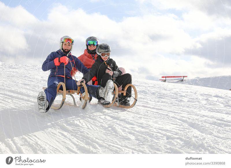 Drei Mädchen haben Rodelspaß Sport Wintersport Berge u. Gebirge Pulverschnee abwärts Skipiste Winterurlaub alpen draußen Schneelandschaft Schneebedeckte Gipfel