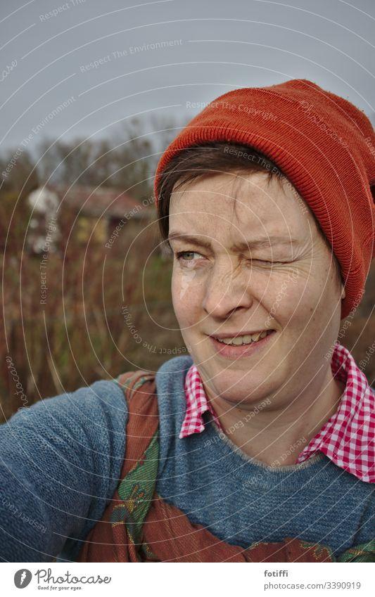 Startklar für die Gartenarbeit Natur Außenaufnahme blinzeln Zwinkern Frau Mütze Tragetuch Porträt feminin Erwachsene selfie