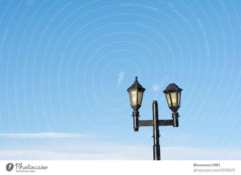 Die Straßenlampe gegen den blauen Himmel mit dem Fernmond Lampenständer zwei Mond Antiquität schwarz Wolken hell aus Tageslicht Paar Großstadt