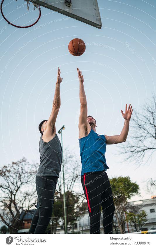 Zwei junge Freunde spielen Basketball. Spiel Jugend Sport Ball Gericht männlich Korb Team Zusammensein aktiv Aktion Spielplatz Übung Männer Freundschaft