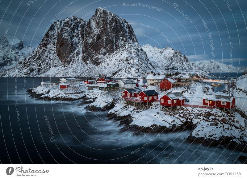 Fischerhütten auf Insel im Fjord auf Felsen mit Schnee vor Bergen mit bewölktem Himmel hat uns ein heimeliges Heim geboten für ein paar wundervolle Tage