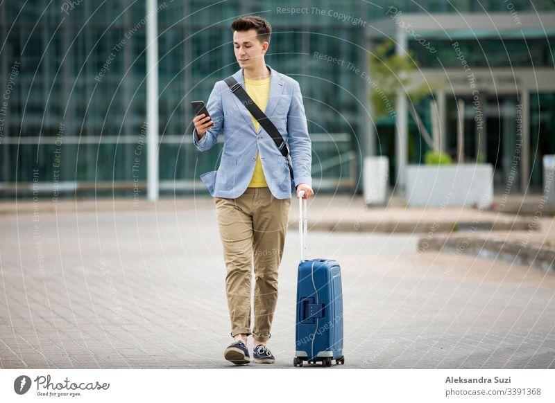 Stylischer Mann steht am Flughafen mit Smartphone und Koffer, blättert, textet, benutzt mobile Apps. Geschäftsreisende. Anwendung Ankunft Tasche Business