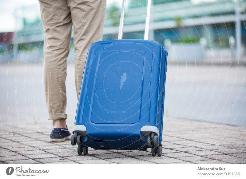 Stilvoller Mann, der mit einem blauen Koffer zum Flughafen geht. Geschäftsmann auf Reisen. Ankunft Tasche Gepäck Gebäude Business führen Fall lässig Großstadt