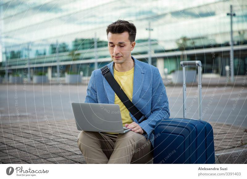 Ein stilvoller Mann sitzt am Flughafen mit Koffer und Laptop, arbeitet, tippt, stöbert. Geschäftsmann auf Reisen. Erwachsener Tasche Gepäck Browsen Business