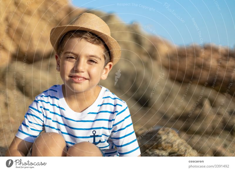 Porträt eines niedlichen Kindes, das auf einem Felsen in der Nähe des Meeres sitzt Anker Baby Hintergrund Strand schön blond blau Junge hell Kaukasier Kindheit