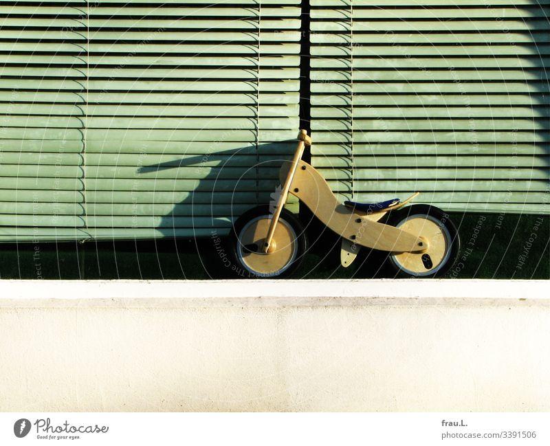 Das kleine Laufrad wartet vor verstaubten Schaufensterrollos sehnsücht darauf, endlich gekauft zu werden Außenaufnahme Spielen Fahrrad warten Rollos allein Holz