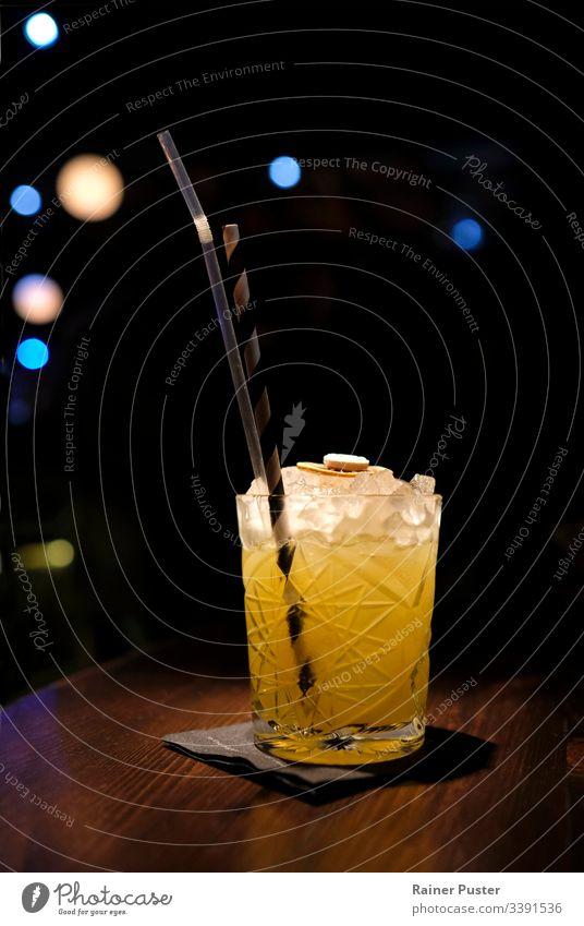 Erfrischender Cocktail in einer Bar mit Bokeh-Licht im Hintergrund Cocktailbar Cocktailglas Erfrischung Nachtleben Eiswürfel Stroh lecker geschmackvoll Coolness