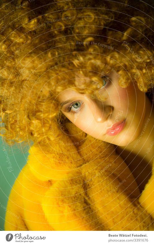 junge Frau mit blonden Locken und gelbem Kunstpelzmantel Schminke Maskenbildner Junge Frau Mode stylisch Straßenkunst Streetstyle trendy flur Pelzmantel