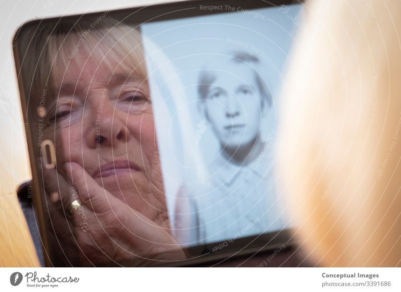 Ältere kaukasische Frau, die sich alte Fotos von sich als junge Frau auf einem Tablet-Computer anschaut Tablet Computer Fotografische Themen Erinnerungen