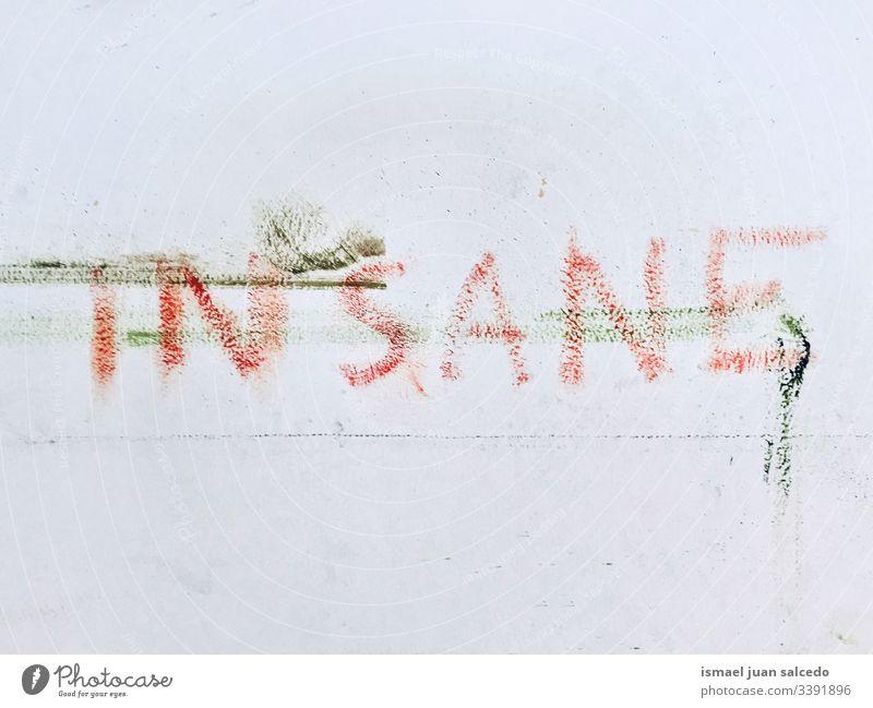 verrücktes Wort auf die schmutzig weiße Wand gemalt Schmutz dreckig wahnsinnig Briefe Wörter Farbe Schriftzeichen Mauer Buchstaben Graffiti Typographie Fassade