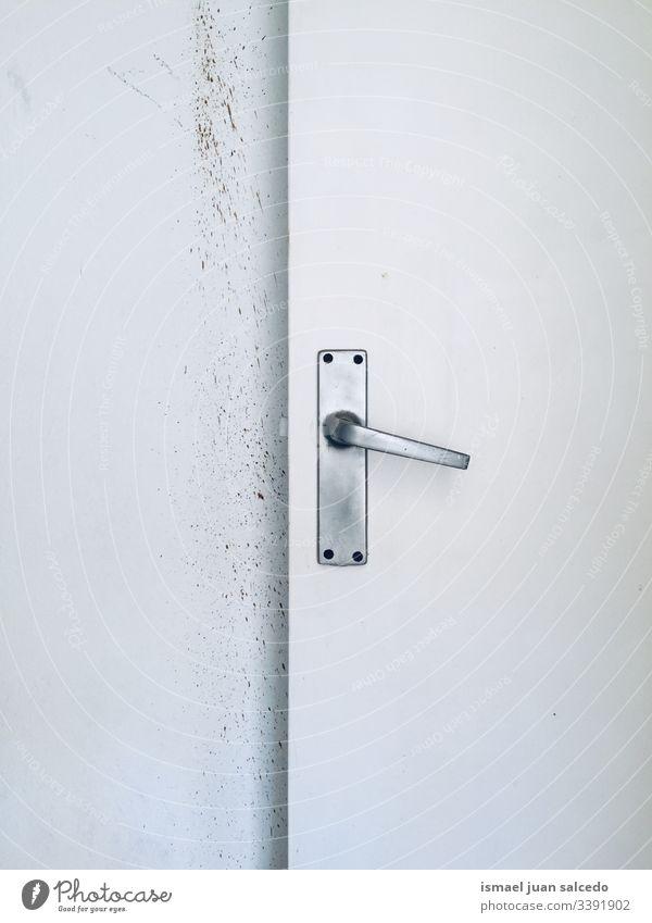 alte weiße Tür im weißen und schmutzigen Raum hölzern dreckig Schmutz im Innenbereich sehr wenige Wand Hintergrund texturiert Türknauf Hand
