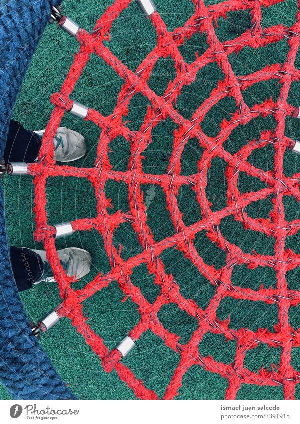 Schaukel mit rotem Seilnetz pendeln Netz Spielplatz Boden abstrakt Kindheit spielerisch lustig Turnschuh Fuß