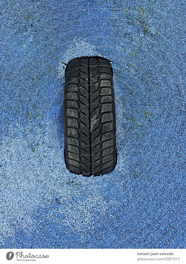 schwarzer Reifen auf blauem Grund Boden Land Schmutz dreckig Hintergründe texturiert Muster abstrakt Oberfläche rau Material alt Verlassen