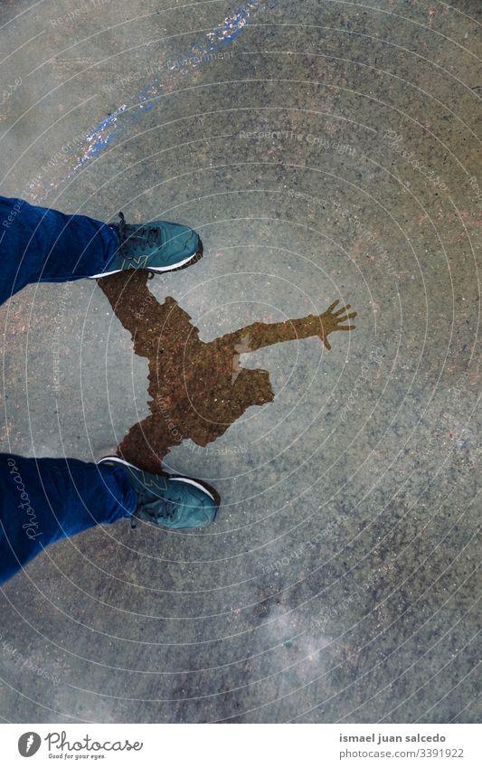 Mann reflektierte auf der Pfütze auf dem Boden, Regentage Person menschlich Fußgänger Wasser regnerisch Reflexion & Spiegelung Schatten Silhouette im Freien