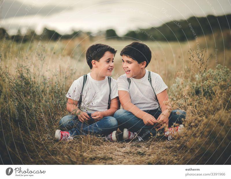 Lächelnde Brüder auf dem Feld sitzend Kinder Jungen Zwillinge Gespräch Geschwister Familie Vereinigung Lifestyle Mittäterschaft Freunde Freundschaft Spaß Spiel