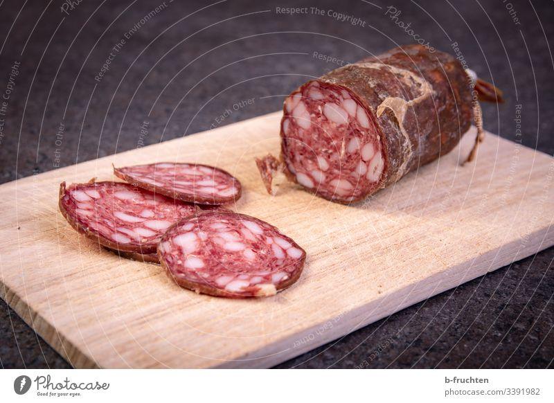 Rohwurst in Scheiben geschnitten auf einem Holzbrett Wurstwaren Jausenzeit Brotzeit Jausenbrett schneiden pause ungesund fett Salami frisch essen Menschenleer
