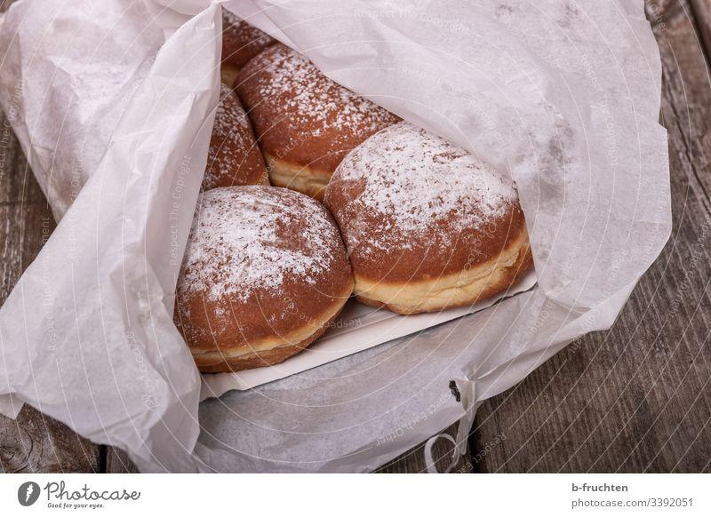 Faschingskrapfen auf Pappteller und mit Papier verpackt papier faschingskrapfen Karneval lecker naschen zucker süssigkeit verpackung verpacken Krapfen Süßwaren