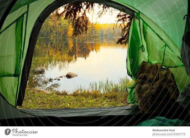Blick aus dem Inneren eines Touristenzeltes mit Rucksack. Wunderschöne skandinavische Wald- und Seenlandschaft. Finnland aktiv Aktivität Abenteuer Herbst Lager