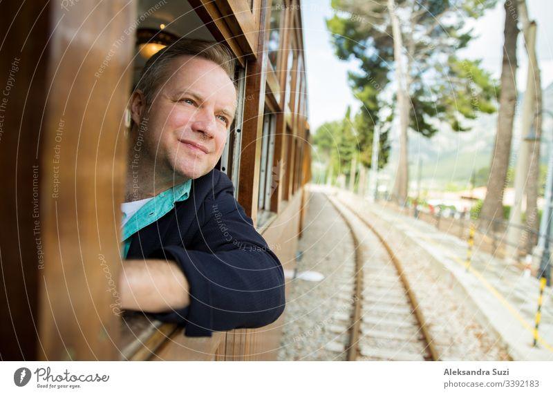Mann, der mit einem Retro-Holz-Zug reist und durch das Fenster schaut. Wunderschöne Berglandschaft. Mallorca, Spanien. Abenteuer allein blond heiter Landschaft
