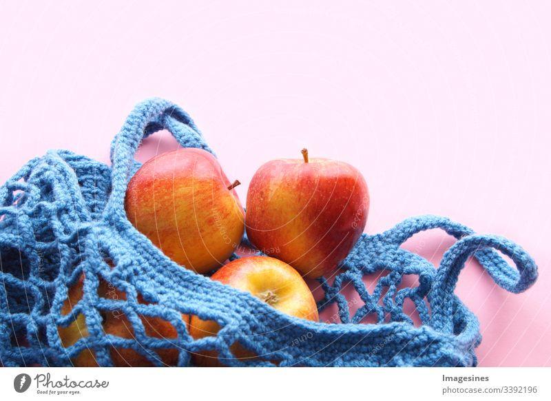 Einkaufsnetz aus Baumwolle - Frei von Kunststoff. wiederverwendbarer Einkaufsbeutel mit Obst - Äpfeln auf rosa Hintergrund. Null Abfall und Ökologie Konzept. umweltfreundlicher Käufer. Ansicht von oben