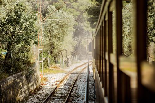 Retro-Holzzug, der entlang einer Eisenbahn in den Bergen fährt. Wunderschöne sonnige Sommerlandschaft. Mallorca, Spanien. Abenteuer Pendler Landschaft