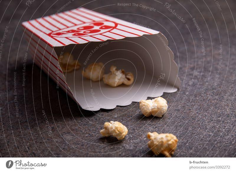 Ein paar Popcorns in einer Tüte am Boden Popkorn Kino Rest Innenaufnahme Lebensmittel Snack lecker Mais Nahaufnahme Fastfood Essen salzig süß Süßwaren ungesund