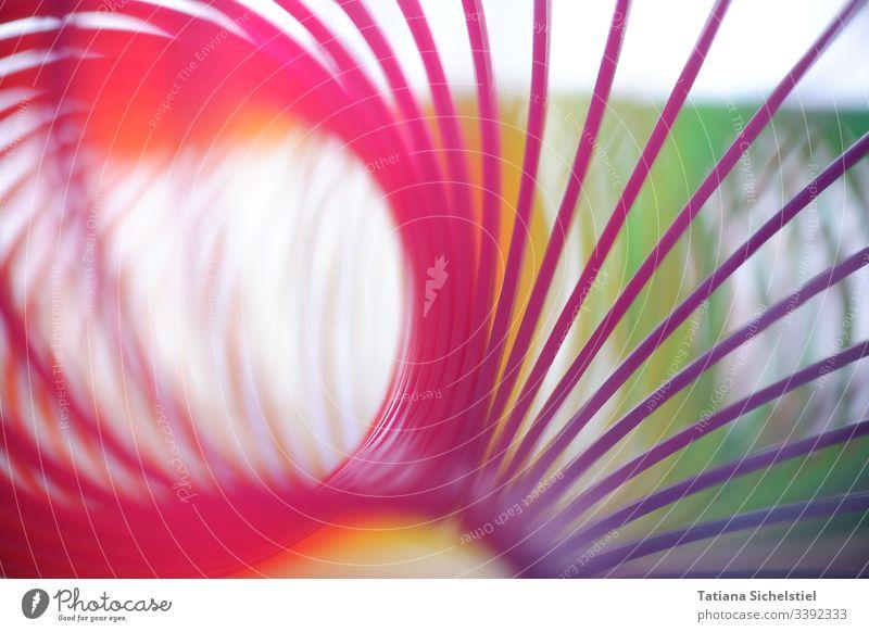 Einzelne Spiralen einer gebogenen Regenbogenspirale / Treppenhüpfer Spielzeug spiralenförmig bunt spiralenlinie mehrfarbig Farbfoto Farbe Nahaufnahme Unschärfe