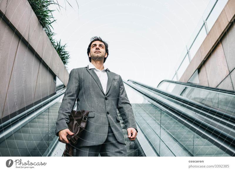Geschäftsmann im Anzug fährt auf einer Rolltreppe Erwachsener Flughafen attraktiv Chef Business Geschäftsleute Geschäftskleidung Großstadt Kaffee korporativ