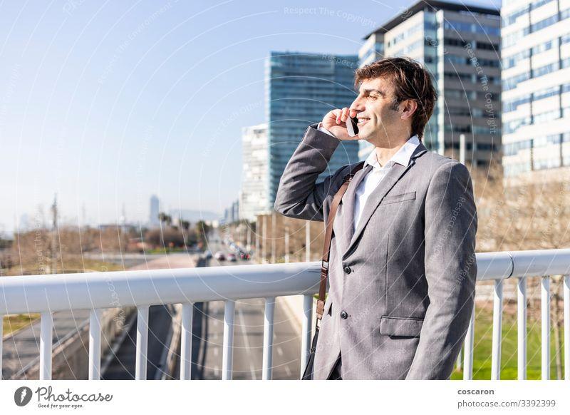 Glücklicher Geschäftsmann mit einem Mobiltelefon in der Stadt Erwachsener Barcelona Brücke Gebäude Business Anruf Funktelefon Großstadt Stadtbild copyspace