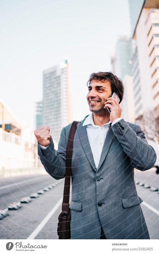 Gutaussehender reifer Geschäftsmann feiert Sieg Errungenschaft Barcelona Vollbart Gebäude Business zu feiern Funktelefon heiter Großstadt Mitteilung Konzept