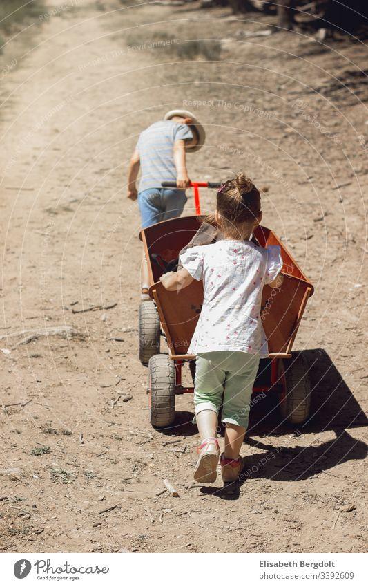 kleiner Junge und kleines Mädchen schieben einen Bollerwagen Urlaub Sommer Kinder Sonnenschein Familie Ausflug Geschwister Draußen entdecken erleben spazieren