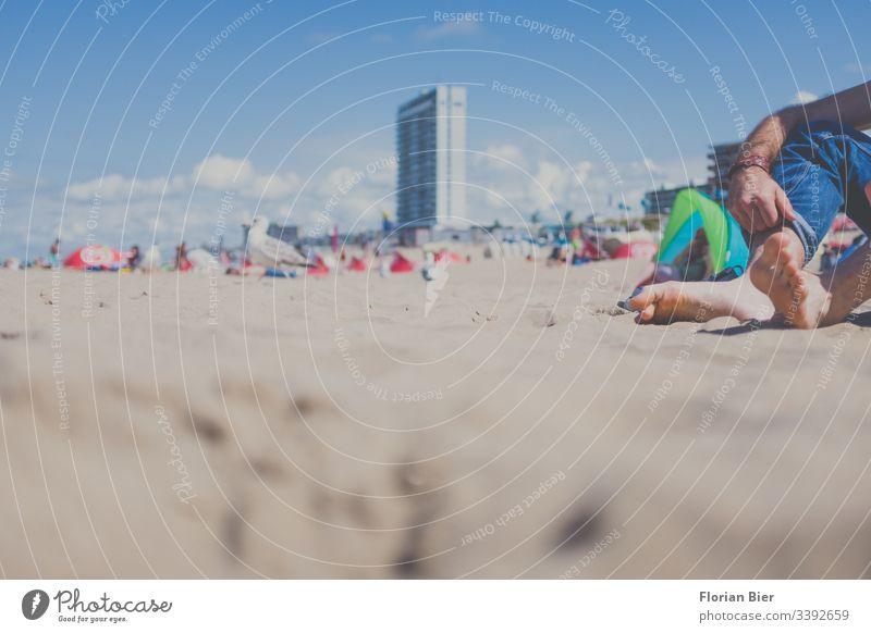 Barfuß bei schönem Wetter mit Hochgekrempelter Hose an einem belebten Strand sitzend Strandleben Gesellschaft Jeans Jeanshose Bekleidung blau lässig Textil Sand