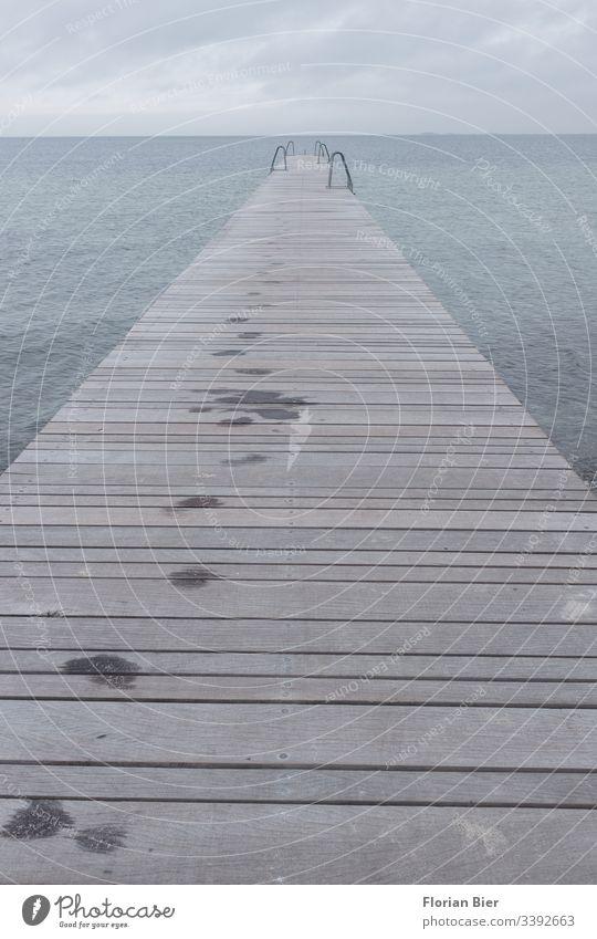 Nasse Fußspuren auf eime Langer Steg mit Badeleitern bei trübem Wetter nass Meer Holzlatten Baden Leiter Wolken regen lang gealtert stabil Wasser See