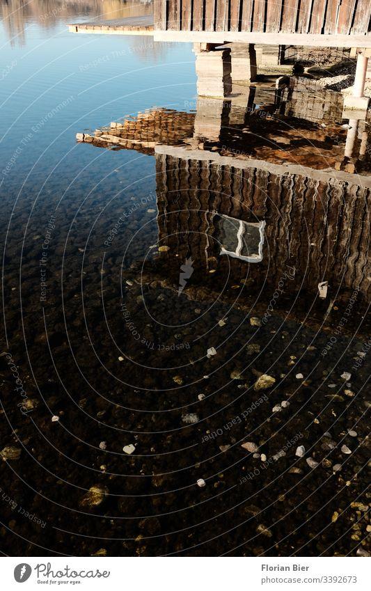 Spiegelung eines Bootshauses aus Holz im flachen Wasser eines Sees Haus Fenster Idylle Wohnen Natur Hütte flaches Wasser Holzbauweise Ferienhaus Anleger Ruhe