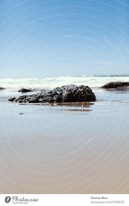 Ein kleines Stück Gestein welches in der Brandung aus dem Sand ragt Stein Felsen Insel Strand Meer Urlaub mediterran Wellen Fantasie Küste Wasser