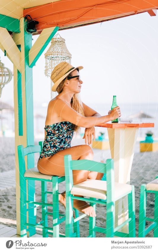 Junge Frau trinkt Bier in einer Strandbar Alkohol allein attraktiv Bar schön Schönheit Getränk blond Flasche lässig Kaukasier heiter selbstbewusst cool