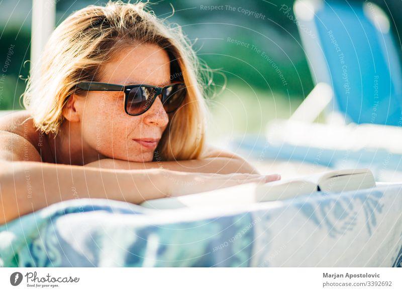 Junge Frau liest ein Buch am Strand liegend attraktiv schön Schönheit Bett blond lässig Kaukasier Nahaufnahme niedlich Tag genießen Sommersprossen Mädchen