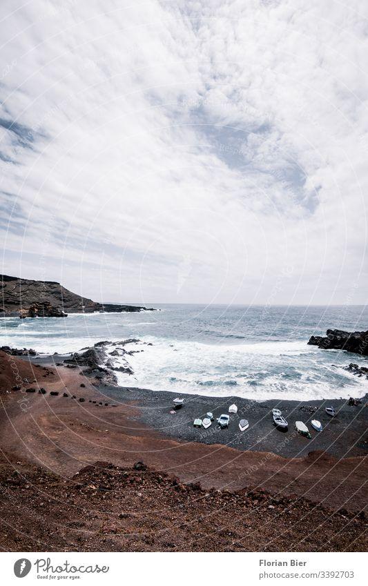 Felsiger Strand mit Fischerbooten und tosendem Meer Felsen Bucht Wasser Wellen gewaltig Stein felsig rauh tief Küste Landschaft Klippe Natur Aussicht Freiheit