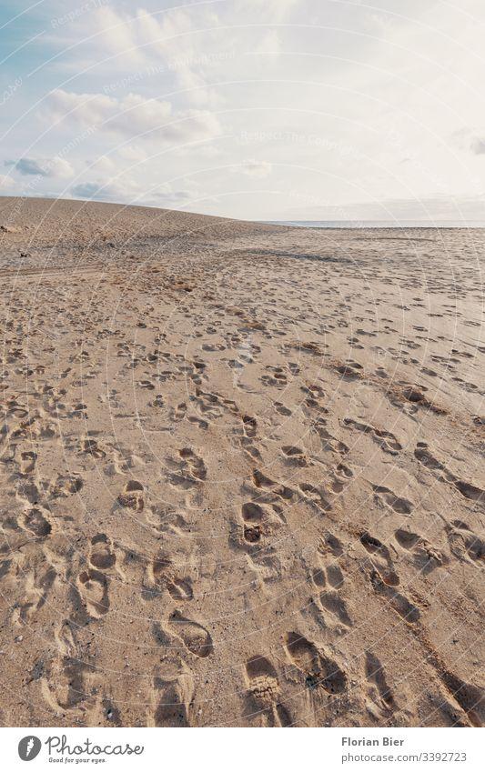 Fußspuhtren auf einer Sanddüne Fußspur Fußgänger Strand Düne Horizont Himmel Wolken Menschen Abdruck Schuhe hinterlassen Spaziergang Spuren Barfuß Einsamkeit
