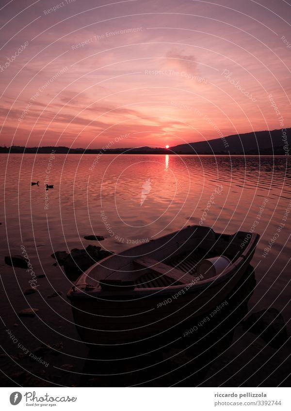 Enten auf einem See mit einem Boot bei Sonnenuntergang Sonnenuntergangssee Silhouette rot purpur Abend Himmel Steine Wolken Schatten Wasser Berge